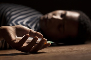 Young african man lying on the floor with a syringe in her hand