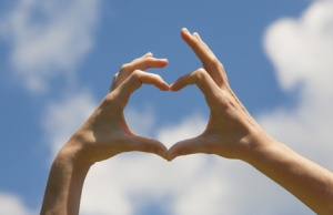 Heart shape hands on the blue sky