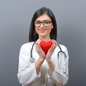 Portrait of young beautiful woman doctor holding red heart against gray background